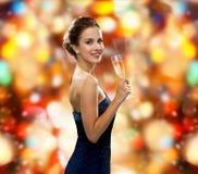Χαμόγελο του ποτηριού εκμετάλλευσης γυναικών του λαμπιρίζοντας κρασιού στοκ εικόνα με δικαίωμα ελεύθερης χρήσης