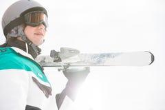Χαμόγελο των φέρνοντας σκι νεαρών άνδρων ενάντια στο σαφή ουρανό στοκ εικόνες