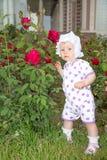 Χαμόγελο όμορφο λίγο κορίτσι παιδιών με το λουλούδι στο πάρκο Στοκ Εικόνες