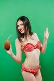 Χαμόγελο Brunette στο φωτεινό μαγιό με το τροπικό κοκτέιλ στα χέρια που θέτουν στο στούντιο στο πράσινο υπόβαθρο Στοκ Εικόνα