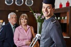 Χαμόγελο concierge με το ανώτερο ζεύγος Στοκ Εικόνες