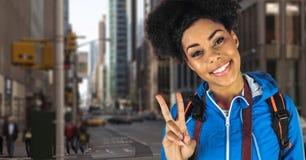 Χαμόγελο hipster του φέρνοντας σακιδίου πλάτης με το gesturing σημάδι ειρήνης καμερών που στέκεται στην πόλη Στοκ Εικόνες