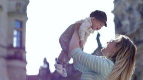 Χαρά της μητρότητας, του νέων mom και του μωρού που γελούν μαζί παίζοντας υπαίθρια φιλμ μικρού μήκους