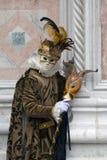 Χαρακτήρας της Βενετίας καρναβάλι σε ένα ζωηρόχρωμες καφετιές και χρυσές κοστούμι και μια μάσκα Βενετία καρναβαλιού στοκ εικόνες