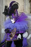 Χαρακτήρας της Βενετίας καρναβάλι σε ένα ζωηρόχρωμες πορφυρές και μαύρες κοστούμι και μια μάσκα Βενετία καρναβαλιού στοκ εικόνα με δικαίωμα ελεύθερης χρήσης