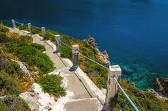 Χαρακτηριστικά ελληνικά άσπρα σκαλοπάτια που οδηγούν στο διαφορετικό κόλπο στην ελληνική ακτή Στοκ φωτογραφία με δικαίωμα ελεύθερης χρήσης