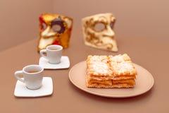 Χαρακτηριστικά ιταλικά fritters Chiacchiere Di Carnevale καρναβαλιού ξεσκόνισαν με κονιοποιημένος Σύνθεση με δύο φλιτζάνια του κα στοκ φωτογραφία