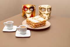 Χαρακτηριστικά ιταλικά fritters Chiacchiere Di Carnevale καρναβαλιού ξεσκόνισαν με κονιοποιημένος Σύνθεση με δύο φλιτζάνια του κα στοκ εικόνες