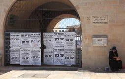 Χαρακτηριστικές αφίσες Haredim και ένας επαίτης Στοκ Φωτογραφίες