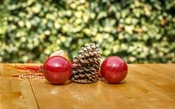 Χαρακτηριστικές διακοσμήσεις Χριστουγέννων δίπλα στο pinecone σε έναν πίνακα Στοκ Φωτογραφίες