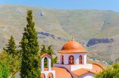 Χαρακτηριστική ελληνική εκκλησία στα βουνά με την Κύπρο στον κήπο, Gre Στοκ Φωτογραφία