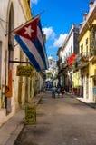 Χαρακτηριστική οδός στην παλαιά Αβάνα με μια μεγάλη κουβανική σημαία Στοκ Φωτογραφίες