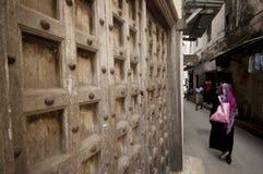 Χαρακτηριστική πόλης οδός Zanzibar με τις παλαιές ξύλινες πόρτες και το wooman περίπατο στοκ εικόνες
