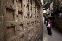 Χαρακτηριστική πόλης οδός Zanzibar με τις παλαιές ξύλινες πόρτες και το wooman περίπατο στοκ φωτογραφία