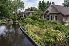 Χαρακτηριστικός η αγροικία με τον όμορφο κήπο κατά μήκος μιας τάφρου σε Giethoorn, γνωστό ως ολλανδική Βενετία Στοκ φωτογραφία με δικαίωμα ελεύθερης χρήσης