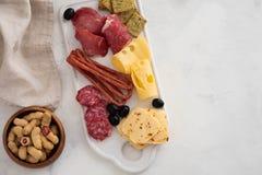 Χαρακτηριστικό ιταλικό antipasto, με το prosciutto, το ζαμπόν, το τυρί και τις ελιές στο άσπρο υπόβαθρο Τοπ άποψη με το διάστημα  Στοκ φωτογραφία με δικαίωμα ελεύθερης χρήσης