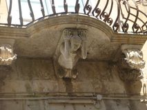 Χαρακτηριστικό μπαλκόνι του Ραγκούσα Ibla με κάτω από ένα άγαλμα που φαίνεται να το κρατά ψηλά Σικελία Ιταλία στοκ εικόνες