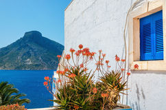 Χαρακτηριστικό μπλε ξύλινο ελληνικό παράθυρο και κόκκινα λουλούδια againt άσπρος-PA Στοκ Φωτογραφίες