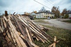 Χαρακτηριστικό ρωσικό τοπίο φθινοπώρου με το καυσόξυλο κοντά στα ragged σπίτια Ρωσικό χωριό Στοκ Φωτογραφίες