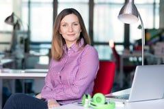 Χαρισματική επιχειρησιακή κυρία στην περιστασιακή συνεδρίαση ιματισμού στον πίνακα γραφείων Στοκ Φωτογραφία