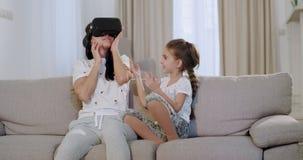 Χαρισματική ώριμη μητέρα με την κόρη της καθμένος στον καναπέ, που χρησιμοποιεί τα γυαλιά μιας εικονικής πραγματικότητας στην εξε φιλμ μικρού μήκους