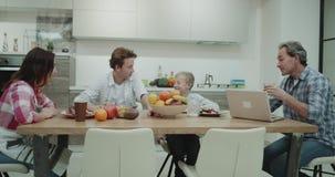 Χαρισματική ώριμη οικογένεια που τρώει τα υγιή τρόφιμα, έχουν μια συνεδρίαση προγευμάτων στον πίνακα γευμάτων ευτυχή ξοδεύοντας έ φιλμ μικρού μήκους