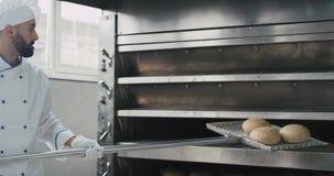 Χαρισματικός αρτοποιός με μια γενειάδα που χρησιμοποιεί έναν ειδικό φανό για να βγάλει το μαγειρευμένο ψωμί από τη βιομηχανική μη φιλμ μικρού μήκους