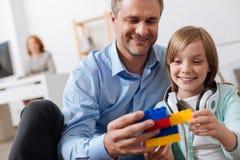 Χαρισματικός ευτυχής μπαμπάς που απολαμβάνει την επιχείρηση παιδιών στην εργασία Στοκ φωτογραφίες με δικαίωμα ελεύθερης χρήσης