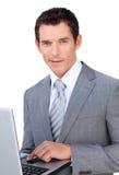 Χαρισματικός νέος επιχειρηματίας που χρησιμοποιεί ένα lap-top Στοκ Φωτογραφίες