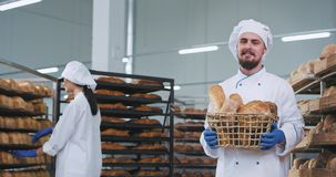Χαρισματικός χαμογελώντας αρτοποιός ατόμων με το πηγούνι που κρατά ένα σύνολο καλαθιών του φρέσκου ψημένου ψωμιού και που φαίνετα απόθεμα βίντεο