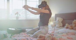 Χαρισματικό νέο κορίτσι εφήβων που χρησιμοποιεί τα γυαλιά μιας εικονικής πραγματικότητας για να έχει μια διασκέδαση στο κρεβάτι τ απόθεμα βίντεο