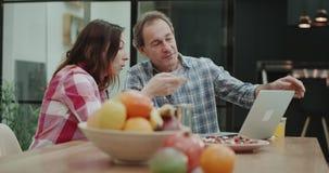 Χαρισματικό ώριμο ζεύγος στην κουζίνα, που κάθεται στον πίνακα γευμάτων και προσεκτική προσέχοντας κάτι στο lap-top φιλμ μικρού μήκους