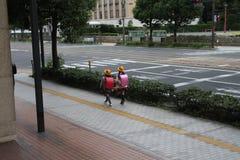Χαριτωμένα δίδυμα ιαπωνικά κορίτσια σπουδαστών στοκ εικόνα