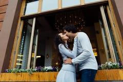 Χαριτωμένα αγκαλιάσματα και φιλιά ζευγών στα πλαίσια ενός ανοικτού παραθύρου ενός καφέ οδών στην πόλη Στοκ Εικόνα