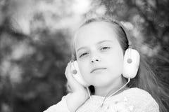 χαριτωμένα ακουστικά κοριτσιών απόλαυσης λίγη χρησιμοποίηση μουσικής Στοκ εικόνα με δικαίωμα ελεύθερης χρήσης