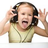 χαριτωμένα ακουστικά κοριτσιών απόλαυσης λίγη χρησιμοποίηση μουσικής Στοκ Εικόνες