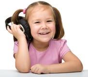χαριτωμένα ακουστικά κοριτσιών απόλαυσης λίγη χρησιμοποίηση μουσικής Στοκ φωτογραφία με δικαίωμα ελεύθερης χρήσης