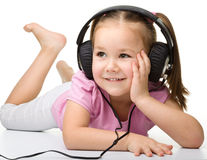 χαριτωμένα ακουστικά κοριτσιών απόλαυσης λίγη χρησιμοποίηση μουσικής Στοκ φωτογραφίες με δικαίωμα ελεύθερης χρήσης