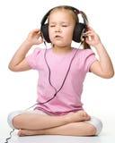 χαριτωμένα ακουστικά κοριτσιών απόλαυσης λίγη χρησιμοποίηση μουσικής Στοκ Φωτογραφία