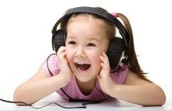 χαριτωμένα ακουστικά κοριτσιών απόλαυσης λίγη χρησιμοποίηση μουσικής Στοκ Εικόνα