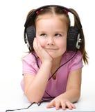 χαριτωμένα ακουστικά κοριτσιών απόλαυσης λίγη χρησιμοποίηση μουσικής Στοκ εικόνες με δικαίωμα ελεύθερης χρήσης