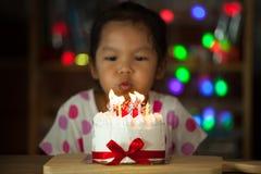 Χαριτωμένα ασιατικά γενέθλια εορτασμού μικρών κοριτσιών και φυσώντας κεριά Στοκ φωτογραφία με δικαίωμα ελεύθερης χρήσης