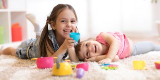 Χαριτωμένα αστεία παιδιά που παίζουν με τα παιχνίδια dishware στο σπίτι στοκ εικόνες