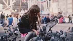Χαριτωμένα ευρωπαϊκά ταΐζοντας πουλιά κοριτσιών από τα χέρια κίνηση αργή Μεγάλο κοπάδι του σπόρου σύλληψης περιστεριών Ευτυχής λί απόθεμα βίντεο