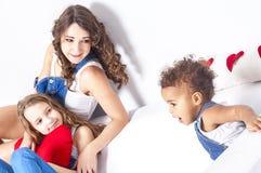 Χαριτωμένα κορίτσια που βρίσκονται στον καναπέ η μητέρα της που έχει τη διασκέδαση Στοκ Εικόνες