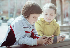 Χαριτωμένα κορίτσια που θέτουν με τα mobiles Στοκ φωτογραφία με δικαίωμα ελεύθερης χρήσης