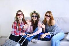 Χαριτωμένα κορίτσια που πηγαίνουν στο ταξίδι και που προετοιμάζουν τις βαλίτσες στον καναπέ μέσα από πίσω Στοκ φωτογραφία με δικαίωμα ελεύθερης χρήσης