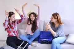 Χαριτωμένα κορίτσια που πηγαίνουν στο ταξίδι και που προετοιμάζουν τις βαλίτσες στον καναπέ μέσα από πίσω Στοκ Εικόνες