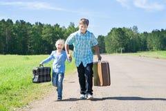 Χαριτωμένα κορίτσι και αγόρι με τη βαλίτσα στοκ φωτογραφίες