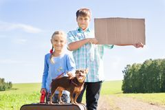 Χαριτωμένα κορίτσι και αγόρι με το σκυλί στο δρόμο στοκ φωτογραφίες